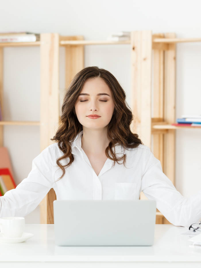 Sky Yoga shala Business and Health Concept: Portrait young woman near the laptop, practicing meditation at the office desk, in front of laptop, online yoga classes, taking a break time for a minute.