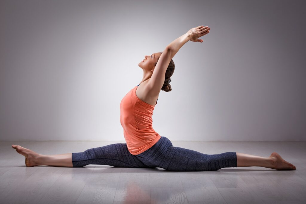 SkyYoga Shala Sporty fit woman doing yoga asana Hanumanasana