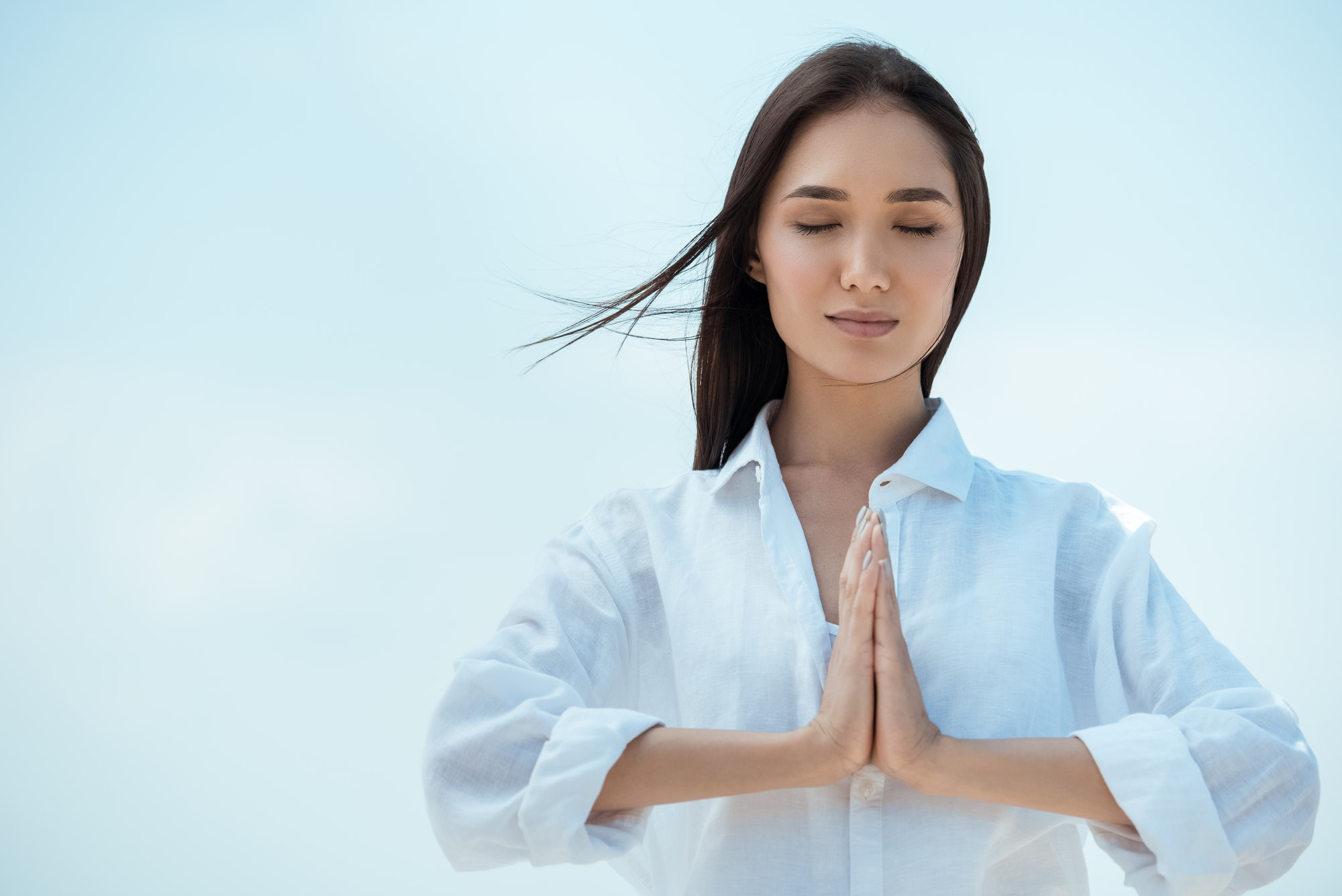 asian woman with closed eyes doing namaste mudra gesture against blue sky