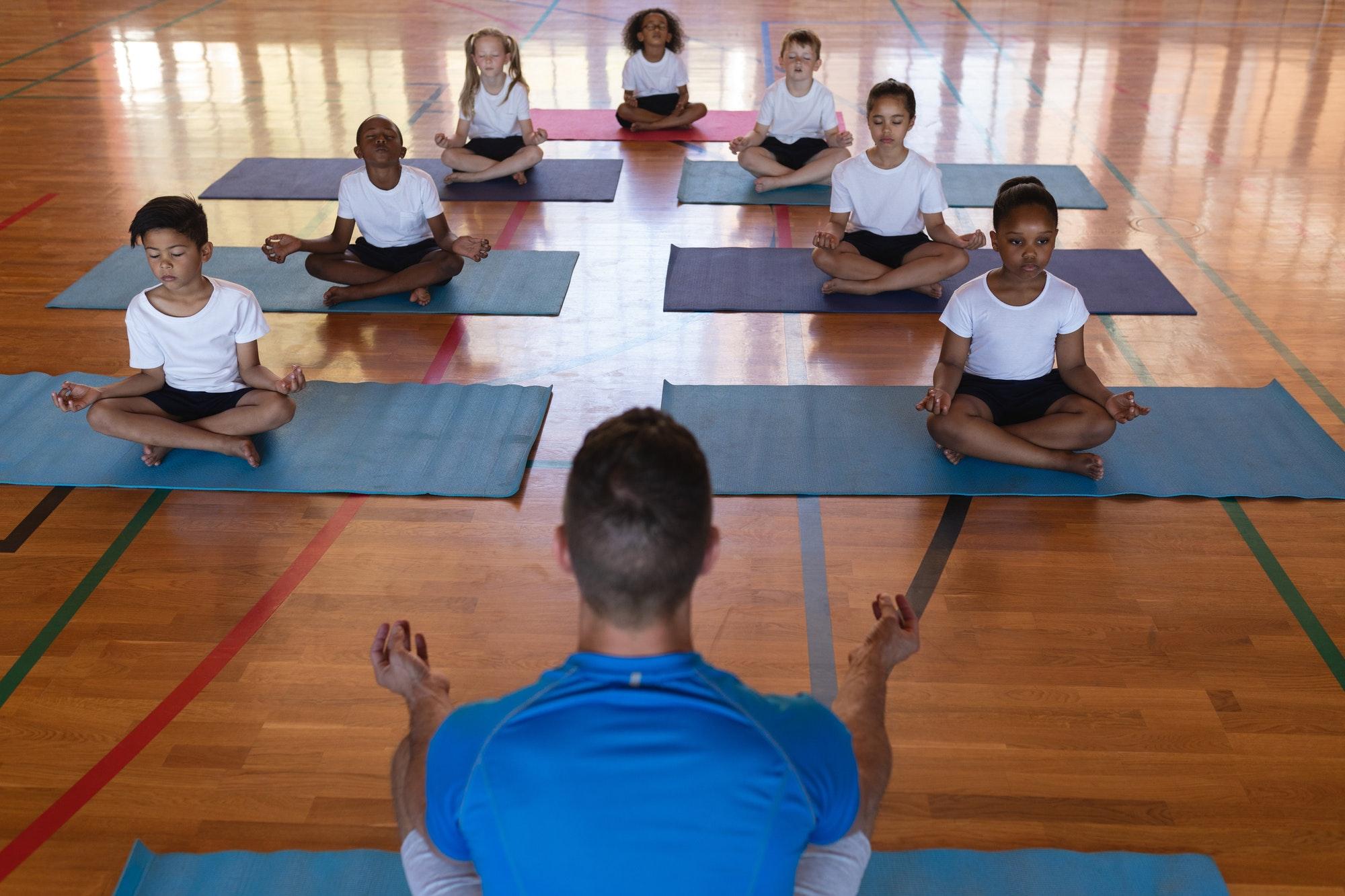 Yoga teacher teaching yoga to school kids in school